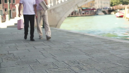 rich male friends with shopping bags in Venice, slow motion