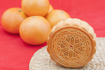 Moon cake on a bamboo mat and some oranges.
