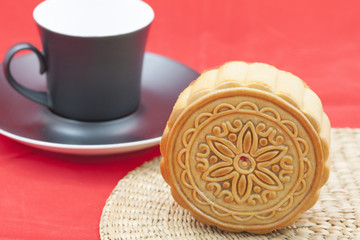 Chinese moon cake on a bamboo mat and a cup of tea.