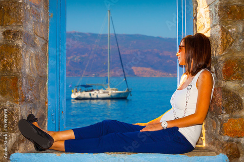 Woman looking view of sailing boat Hydra Island in Greece