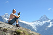 Girl sitting on a rock against Swiss Alps
