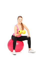 A smiling female lifting up a dumbbell seated on a fitness ball