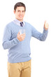 Casual guy holding a glass of water and giving thumb up