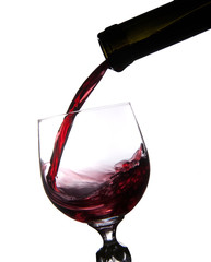 Pouring wine into glass isolated on white
