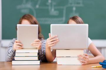 zwei schülerinnen lesen mit laptop und tablet-pc