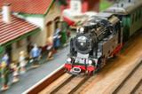 express steam train speeding through a station