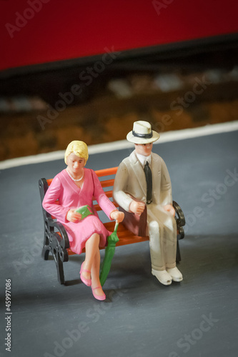 miniature people sitting on a railway station bench