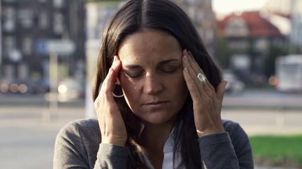 Tired businesswoman having headache in the city