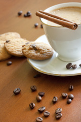 Cappuccino with chocolate cookies on wooden table
