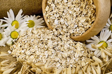 Oat flakes in a wooden bowl with chamomiles