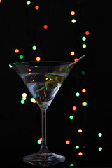Martini glass and olives on dark bright background