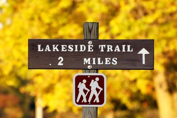 Hiking trail sign with yellow autumn foliage