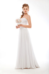 Bride in white couture wedding dress with flowers posing