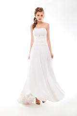 Beautiful woman in wedding dress over studio background