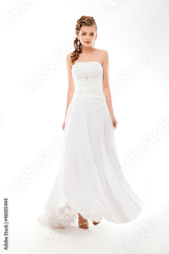 Beautiful woman in wedding dress over studio background