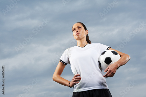 Fußballerin mit Fußball vor Himmel