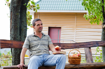Thoughtful man eating an apple outdoors