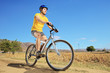 A young male in yellow shirt riding a bike