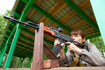 Young woman aiming at a target and shooting an automatic rifle f