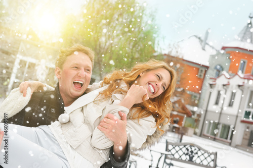 Winter couple piggyback in snow smiling happy and excited. Beaut