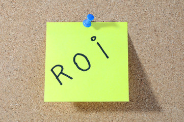 The word ROI Note paper with push pins on noticeboard