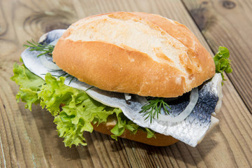 Fresh Herring on a roll (wooden background)