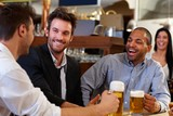 Young businessmen drinking beer at pub