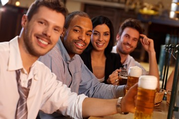 Happy young people sitting in pub, drinking beer