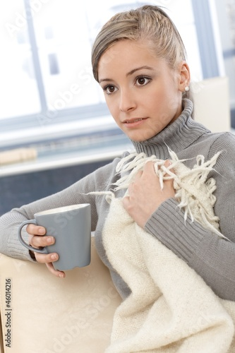 Young woman resting on sofa with tea