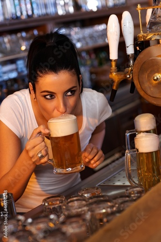 Young female bartender tasting draft beer