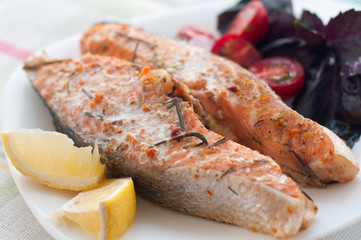 salmon steak with cherry tomatoes basil and lemon