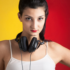 Girl with headphones against red and yellow background.