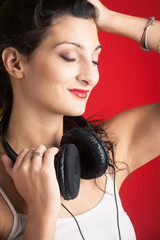 Beautiful girl with headphones against red background.