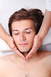 Handsome man enjoying face massage in spa salon