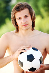 Young and handsome guy with soccer ball on the beach