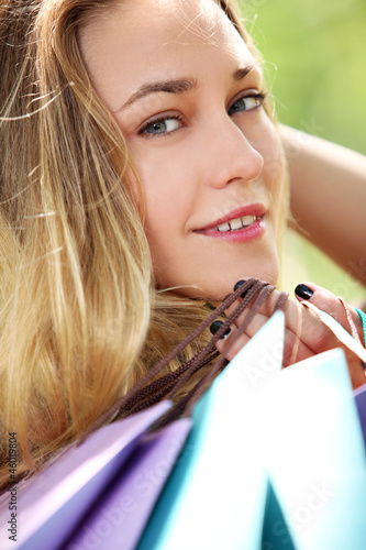 Beautiful smiling girl in park with shopping bags