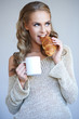 Cute girl holding white cup  and croissant while isolated