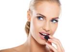 Close up of beautiful woman eating blackberries