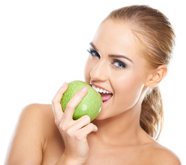 Beautiful  young woman bites a green apple