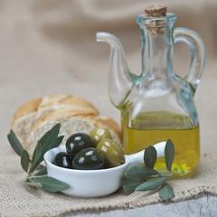 Aceite de oliva y aceitunas con pan sobre arpillera y madera