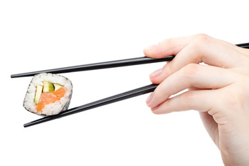 Hand holding fresh maki sushi roll with black chopsticks
