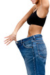 Body of a slim girl wearing huge jeans, isolated on white