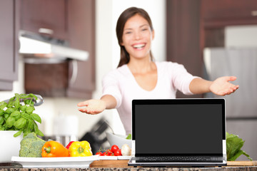 Woman cooking showing laptop in kitchen