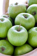 green granny smith apples in a wooden trug
