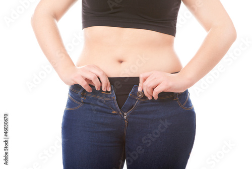 Size 40 woman zipping jeans, obesity and overweight concept