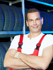 Master mechanic in a tire warehouse is proud of the service