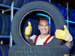 Funny car mechanic stores winter tires and shows thumb up