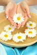 woman hands with wooden bowl of water with flowers,