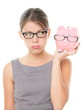 Upset woman wearing glasses holding piggy bank