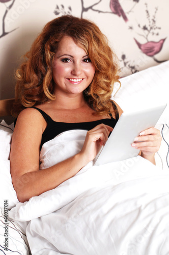 Young Woman in Bed with a Tablet PC